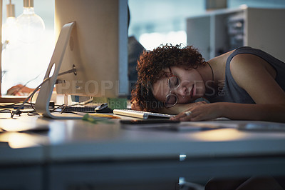 Buy stock photo Cropped shot of a young businesswoman taking a nap on her desk in a modern office at night