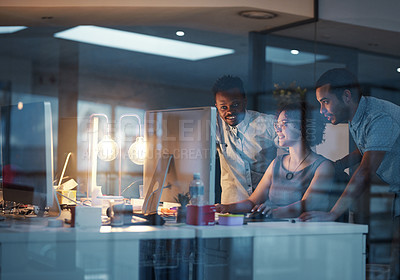 Buy stock photo Cropped shot of young colleagues working in a modern office at night