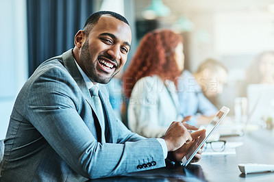 Buy stock photo Portrait of a young businessman using a digital tablet during a meeting in an office