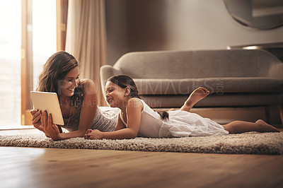 Buy stock photo Shot of a young woman and her adorable daughter using a digital tablet while relaxing on the floor at home