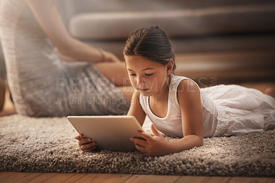 Buy stock photo Shot of an adorable little girl using a digital tablet on the floor at home with her mother in the background