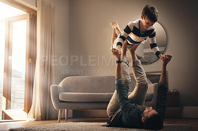 Buy stock photo Shot of a young man enjoying playtime with his son at home