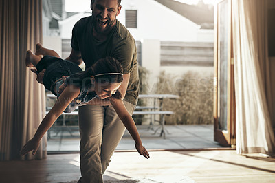 Buy stock photo Shot of a young man enjoying playtime with his daughter at home