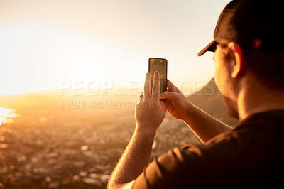 Buy stock photo Rearview shot of an unrecognizable young man taking photographs during his hike in the mountains