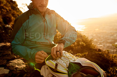 Buy stock photo Cropped shot of an unrecognizable young man taking a break during his early morning hike in the mountains