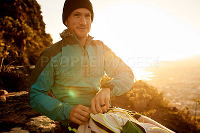 Buy stock photo Cropped shot of a young man taking a break during his early morning hike in the mountains
