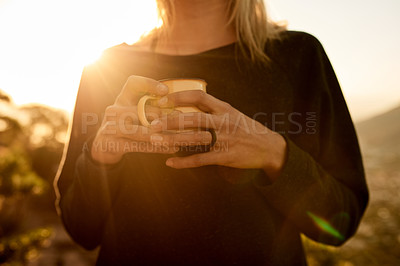 Buy stock photo Cropped shot of an unrecognizable young woman taking a coffee break during her mountain hike