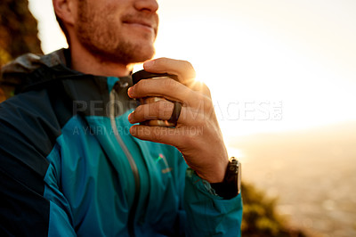 Buy stock photo Cropped shot of an unrecognizable young man taking a coffee break during his mountain hike