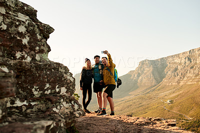 Buy stock photo Full length shot of three young friends taking selfies during their hike in the mountains