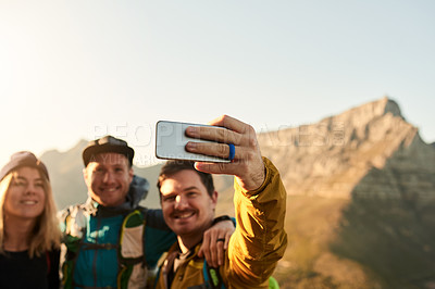 Buy stock photo Cropped shot of three young friends taking selfies during their hike in the mountains