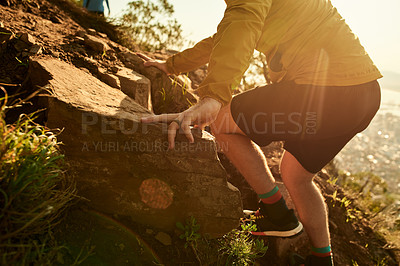 Buy stock photo Cropped shot of an unrecognizable young man scaling a cliff during an early morning hike in the mountains