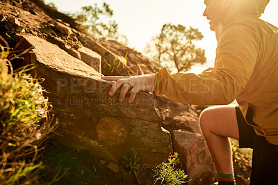 Buy stock photo Cropped shot of a young man scaling a cliff during an early morning hike in the mountains