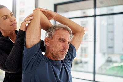 Buy stock photo Shot of a focussed middle aged man doing stretching exercises with his personal trainer inside of a gym during the day