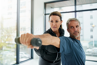Buy stock photo Shot of a focussed middle aged man doing weight exercises with his personal trainer inside of a gym during the day