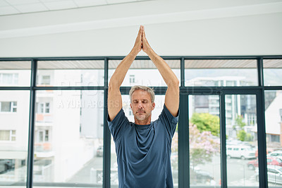 Buy stock photo Shot of a focussed middle aged man doing yoga poses while stretching his arms in the air inside of a studio during the day