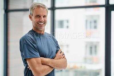 Buy stock photo Portrait of a confident middle aged man standing with his arms folded inside of a studio during the day