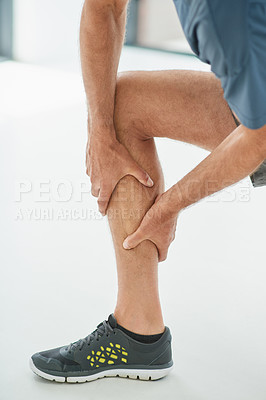 Buy stock photo Shot of an unrecognizable man holding his leg due to pain while kneeling on the floor inside of a studio during the day