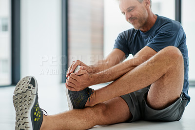 Buy stock photo Shot of an uncomfortable looking middle aged man touching his foot due to pain while being seated on the floor of a fitness studio during the day