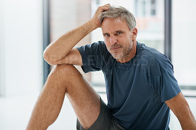 Buy stock photo Portrait of an exhausted looking middle aged man seated on the floor of a fitness studio while contemplating during the day