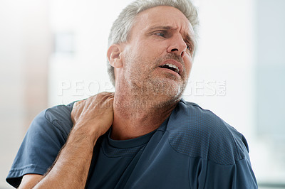 Buy stock photo Shot of a stressed out middle aged man holding his shoulder due to pain inside of  a fitness studio