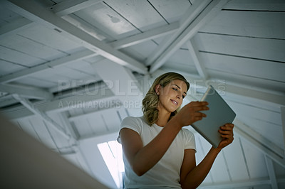 Buy stock photo Low angle shot of an attractive young woman using a digital tablet during a relaxing day at home