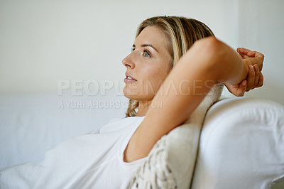 Buy stock photo Shot of a thoughtful young woman relaxing on the sofa at home