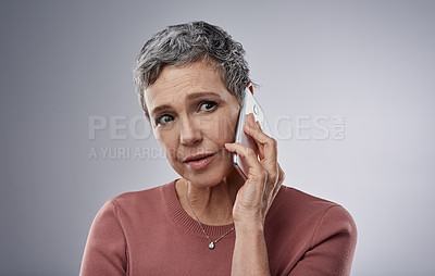Buy stock photo Studio shot of a mature woman using a mobile phone and looking concerned against a gray background