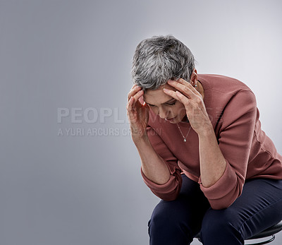Buy stock photo Studio shot of a mature woman experiencing stress against a gray background