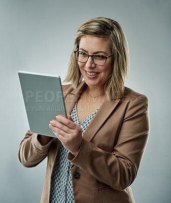 Buy stock photo Studio shot of an attractive young businesswoman using a digital tablet against a gray background