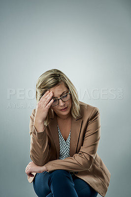 Buy stock photo Studio shot of a young businesswoman looking stressed against a gray background