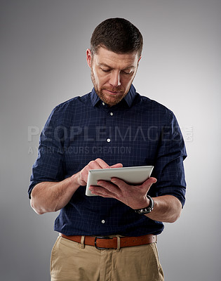 Buy stock photo Studio shot of a handsome young man using a tablet against a grey background