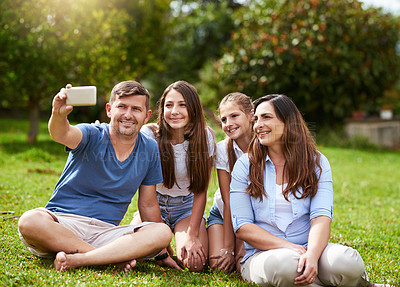 Buy stock photo Shot of a cheerful family seated in a park while taking a self portrait together outside during the day