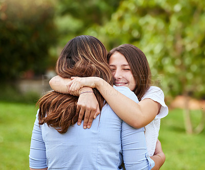 Buy stock photo Shot of a cheerful young mother and daughter giving each other a hug while standing outside in a park during the day