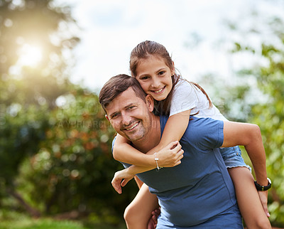 Buy stock photo Portrait of a cheerful young man giving his daughter a piggyback ride outside in a park during the day