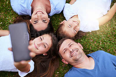 Buy stock photo Portrait of a cheerful family lying on the ground while taking a self portrait together outside in a park during the day