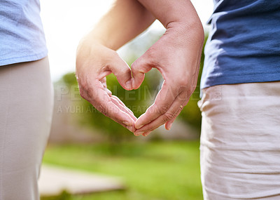 Buy stock photo Closeup of two unrecognizable people forming a heart together with their hands while standing outside in a park during the day