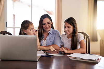 Buy stock photo Shot of two cheerful young girls doing homework around a table while getting help from their mother at home during the day