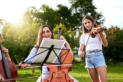 Buy stock photo Shot of a young girl playing a violin outdoors