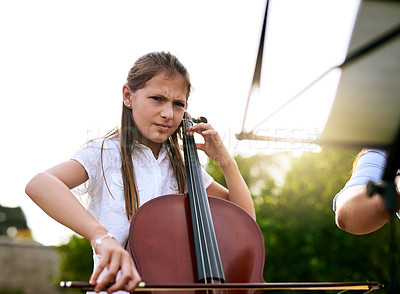 Buy stock photo Shot of a determined young girl playing the cello while standing in the backyard of her home during the day