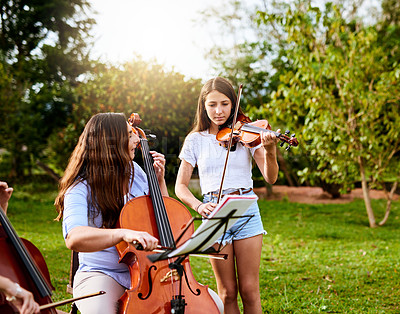 Buy stock photo Shot of a determined young mother and daughter playing classical string instruments together in their backyard at home during the day