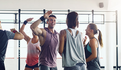 Buy stock photo Shot of a group of young people motivating each other with a high five in a gym