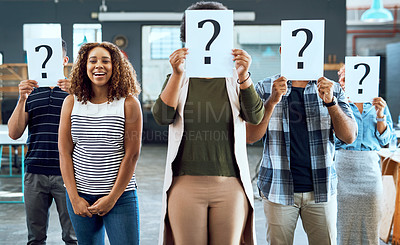 Buy stock photo Portrait of a young businesswoman standing amongst her colleagues holding up placards with question marks on in an office