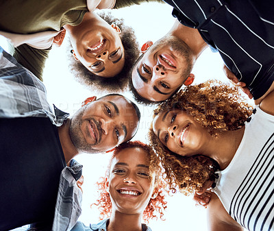 Buy stock photo Low angle shot of a group of businesspeople joining their heads together in a huddle