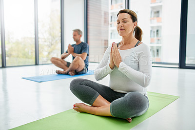 Buy stock photo Shot of a focussed middle aged couple seated on exercise mats on the floor while doing yoga poses inside of a fitness studio during the day