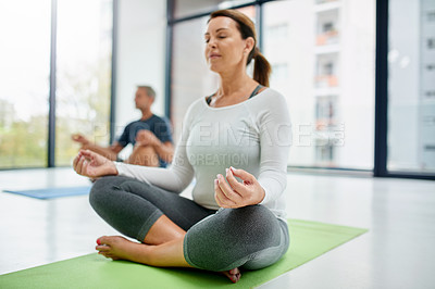 Buy stock photo Shot of a focused middle aged woman seated on a exercise mat with her legs crossed while doing yoga poses inside of a fitness studio