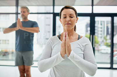 Buy stock photo Shot of a focussed middle aged couple doing yoga poses together while standing inside of a fitness studio during the day