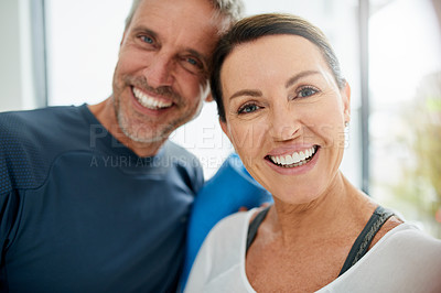 Buy stock photo Portrait of a cheerful middle aged couple standing together with their exercise mats after doing yoga and taking a selfie inside of a fitness studio
