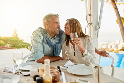 Buy stock photo Shot of a cheerful middle aged couple enjoying a glass of wine together while being seated at a table outside at a restaurant