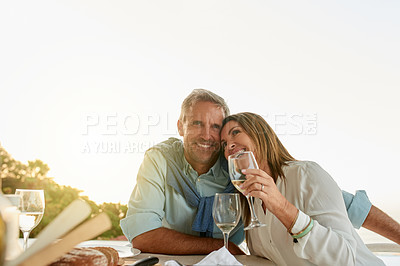 Buy stock photo Portrait of a cheerful middle aged couple enjoying a glass of wine together while being seated at a table outside at a restaurant