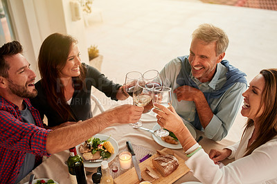 Buy stock photo Shot of a group of cheerful people having dinner together around a table while having a celebratory toast with wine